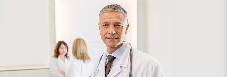 A doctor, with grey hair and a white blouse, smiles.